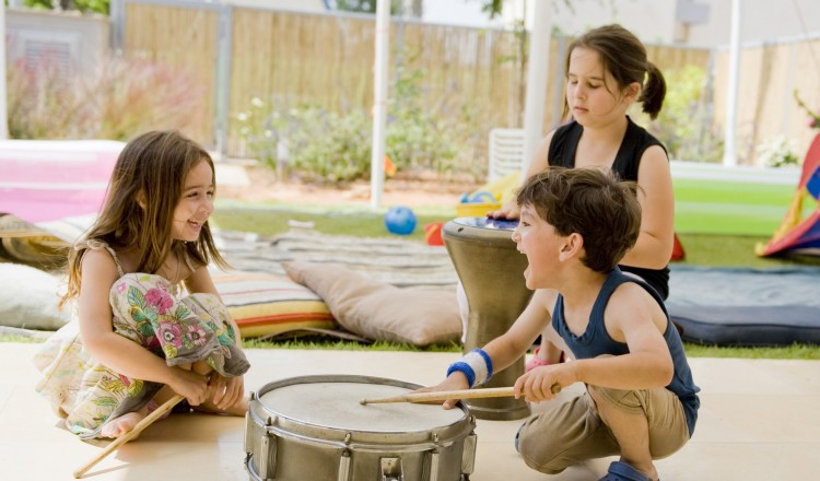 three kids having fun with drums